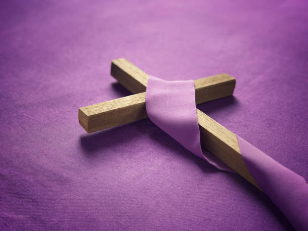 A religious cross placed on purple background.